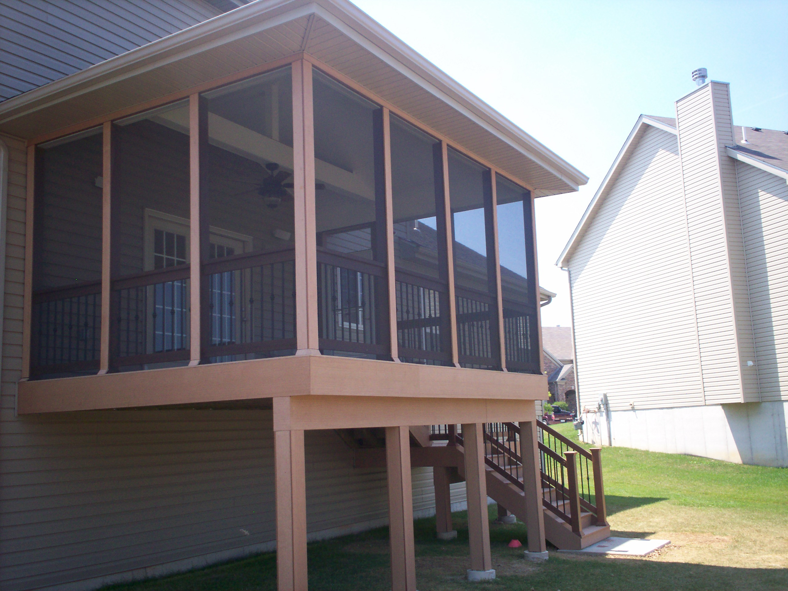 This second story screened porch features composite decking and rails with  black Deckorator aluminum balusters.The open gable roof and wide screen